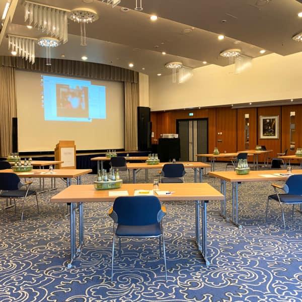 Aufbau einer Hybrid Konferenz mit Tischen, Pult und Leinwand