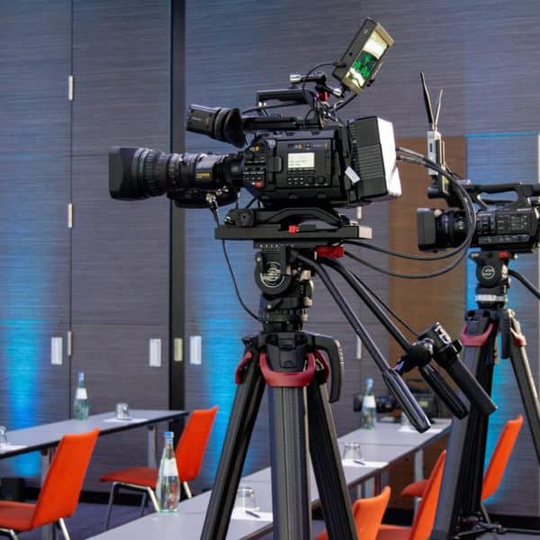 Zwei hochprofessionelle Kameras im hinteren Bereich des bestuhlten Tagungsraums