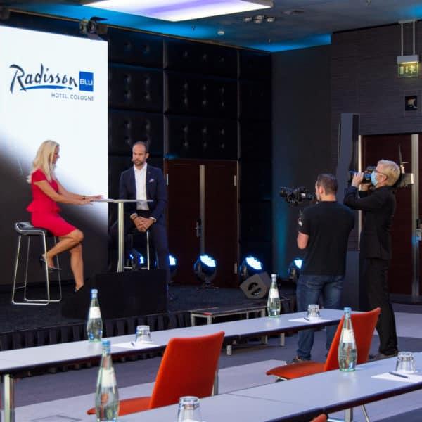 Moderatorin im Dialog auf der Bühne vor einer Leinwand. Zwei Kameramänner filmen die Szenerie, die live übers Internet übertragen wird.
