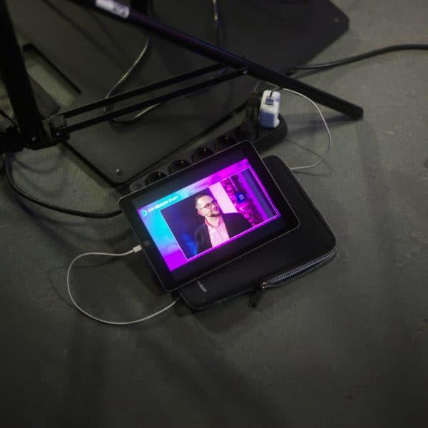 Referenzfoto in der Rotunde in Bochum. Es zeigt ein Tablet auf dem der Live-Stream des Digi Health Care Online Events zu sehen ist.