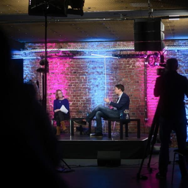 Bühnensituation mit Moderation und Redner. Der Kameramann filmt die ausgeleuchtete Kulisse.