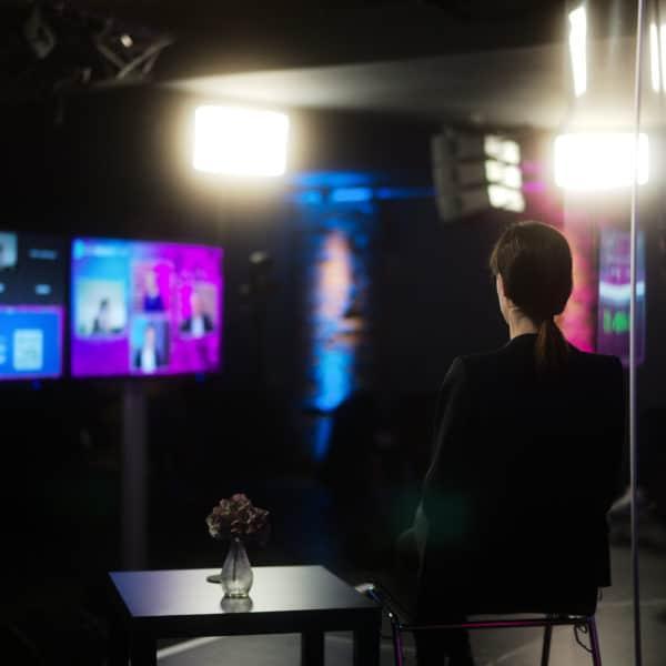 Sicht einer Moderatorin von der Bühne auf die Displays und den Regiebereich hinter der Kamera.