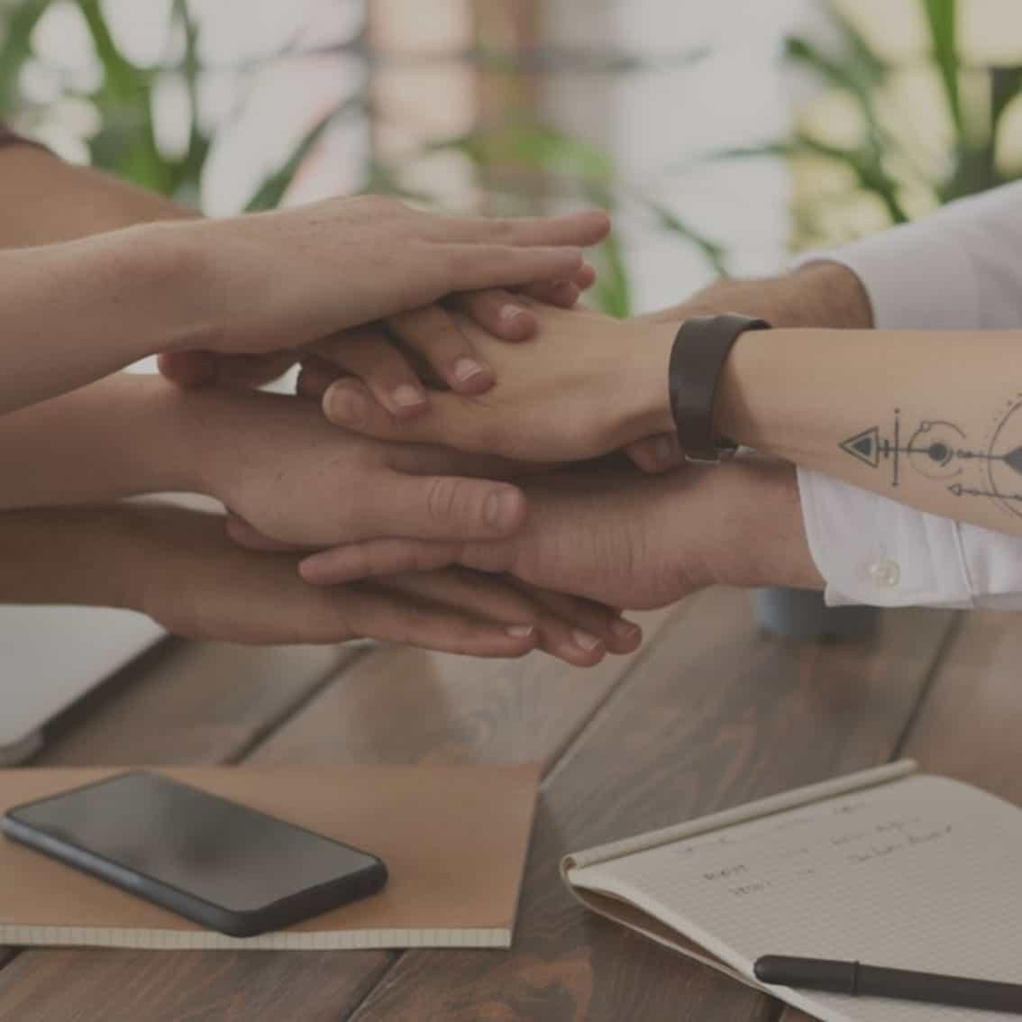 Team Hände aufeinander bei Veranstaltungen wie Workshops und Gruppenarbeiten